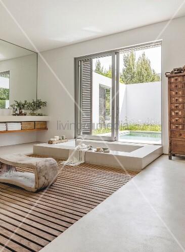 Sunken bathtub in elegant bathroom with view of pool