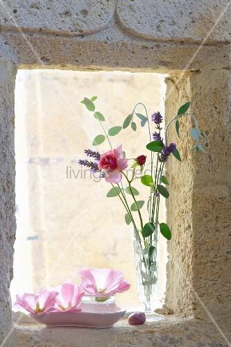 Vase mit zarte Rose und Lavendelblüten auf Fensterbank