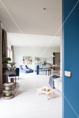 Blue sliding door leading into open-plan interior with sofa and dining table