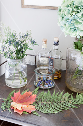 Sycamore and fern leaves amongst flowers and bottles of spirits on table