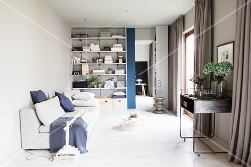 Living room in shades of grey with shelves and sliding door