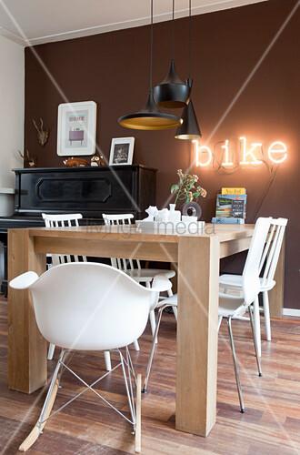 Verschiedene weiße Stühle um den Holztisch vor brauner Wand