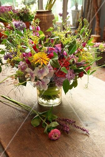 Bunter Sommerblumenstrauß in Glasvase auf Holztisch