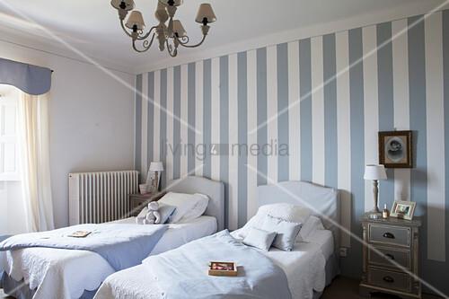 Zwei Einzelbetten im blau-weißen Schlafzimmer mit gestreifter Wand
