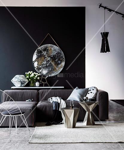 Stuhl, silberne Beistelltische und Sofa vor Konsolentisch mit Skulptur aus Marmorpapier und Tulpenstrauß, rundesKunstwerk in Metallic-Optik