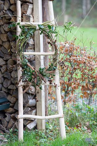 Wreath of Cornus, Ilex and various cones on ladder