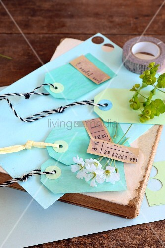 Gebastelte Papieretikettten in Blau- und Grüntönen auf einem alten Buch
