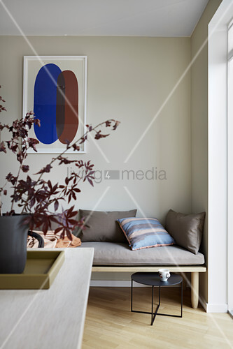 Leafy branches on dining table in front of wooden bench with cushions