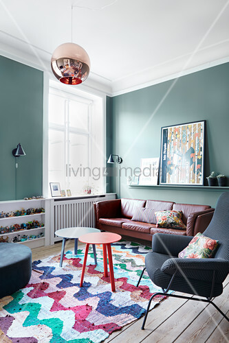Petrol-blue walls and patterned rug in living room