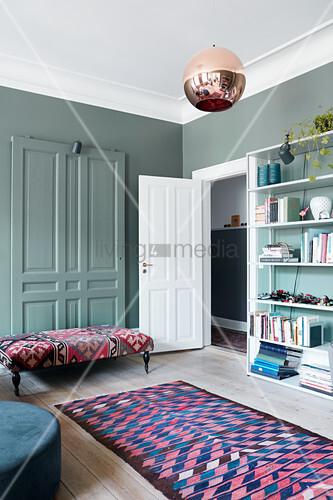 Stilmix und petrolblaue Wand im Wohnzimmer mit Kassettentüren