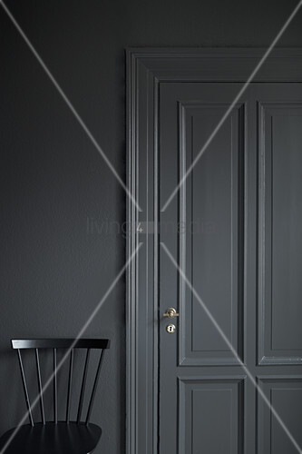 Black chair against grey wall with grey panelled door