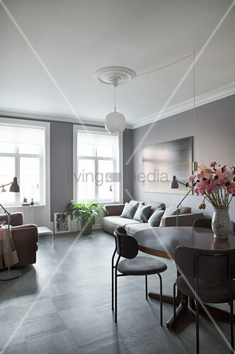 Sofa behind flowers on dining table in living room in shades of grey
