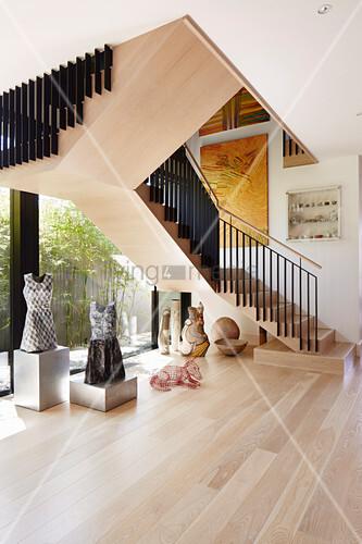Skulpturensammlung auf dem hellen Holzboden unter der Treppe