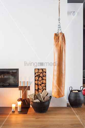 Punching bag suspended next to fireplace and firewood store