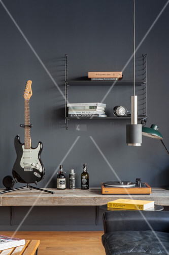 Guitar and record player on deep shelf mounted on grey wall