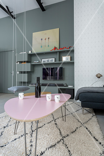 Pink retro table in living room with swing seat in background