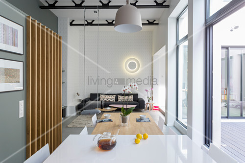 View across dining table into living space of loft apartment