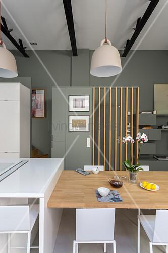 Esstisch im modernen, offenen Wohnraum mit Trennwand zur Haustür