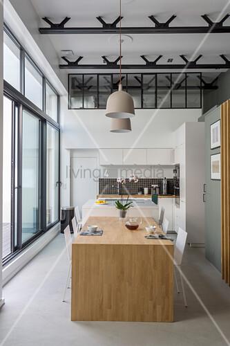 Esstisch aus Holz in Verlängerung zur Kücheninsel im Loft mit Glasfront