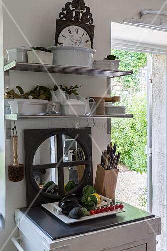 Regal mit Geschirr, Spiegel, Messerblock und Gemüseplatte in rustikaler Küche