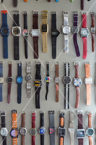 Sammlung von Armbanduhren hängt in Reihen an grauer Wand