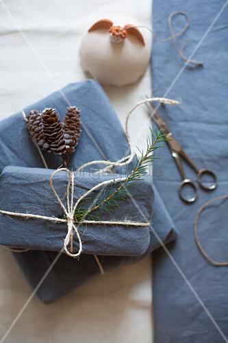 In blauen Stoff verpackte Geschenke mit Paketschnur und Zapfen