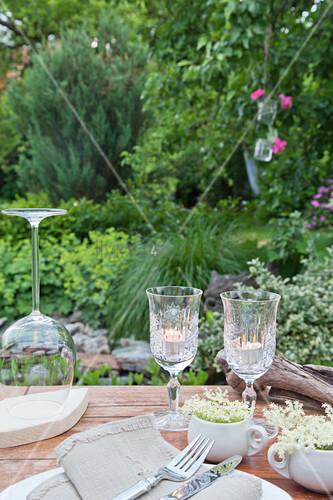 Weingläser als Windlichter auf gedecktem Tisch im Garten