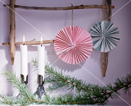Paper rosettes hung from wooden ladder next to candles on conifer branch