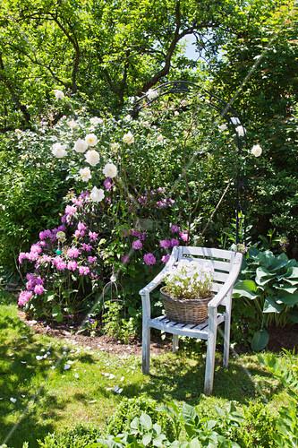 Mit Blumen bepflanter Korb auf einem Stuhl im Sommergarten