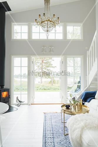 Kronleuchter und Kaminofen in hohem, weißem Wohnzimmer mit Terrassentür