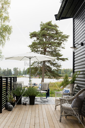Wicker furniture on wooden deck with view of lake
