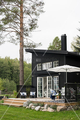 Wooden house with single-pitch roof, lattice doors and terrace with parasol