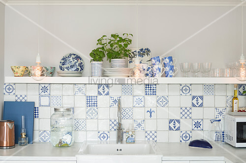 White and blue wall tiles and shelf above sink in kitchen