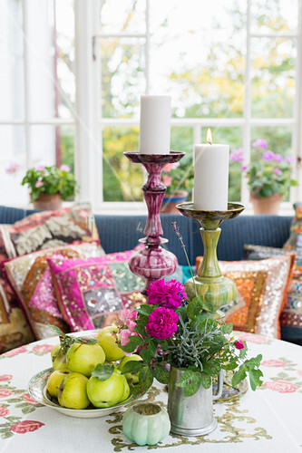 Fruit, flowers and candles on round table in front of sofa with colourful scatter cushions on conservatory