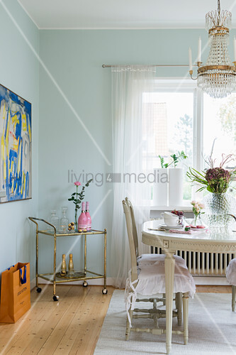 Antique Swedish dining table, chairs and serving trolley in dining room with mint-green walls