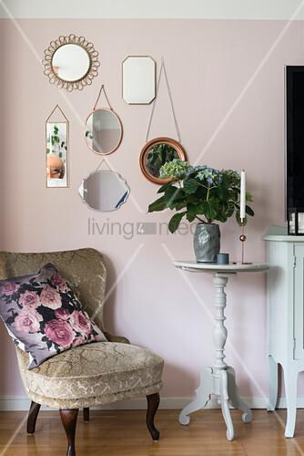 Alter Sessel vor rosafarbener Wand mit Spiegelsammlung