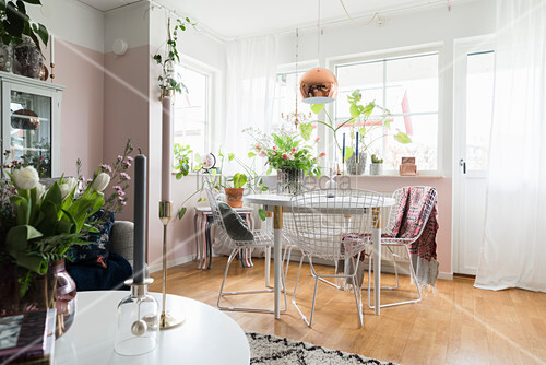 Filigrane Metallstühle um den Esstisch vor rosafarbener Wand