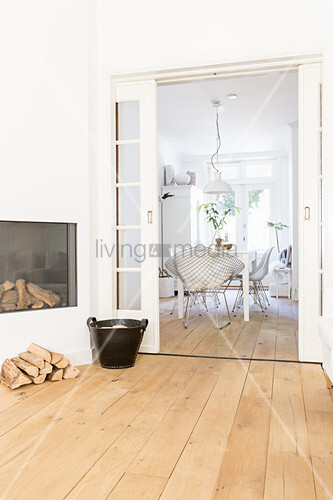 Firewood in front of fireplace and view into dining room through open sliding doors