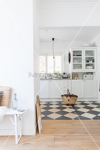 White kitchen with black and white chequered marble floor tiles