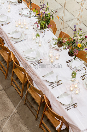 Flower arrangements suspended over festively set dining table in converted barn
