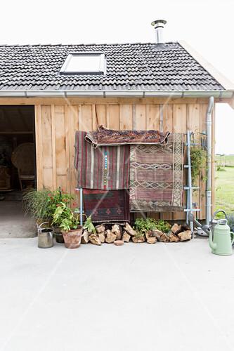 Ethnic rug hung from frame outside barn