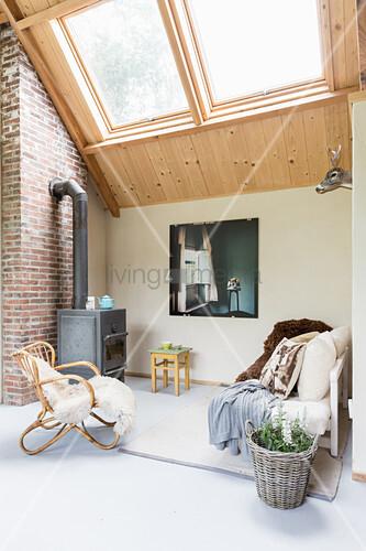 Log burner in seating area in niche below skylights