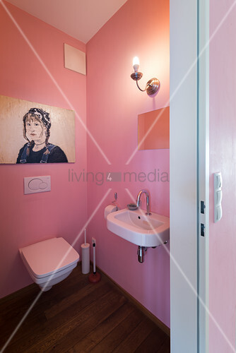 Sconce lamp and pink walls in guest toilet