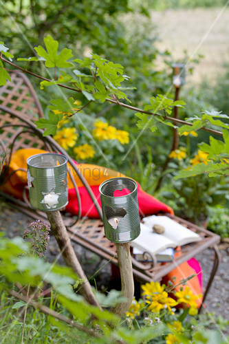 Candle lanterns hand-made from tin cans attached to branches in garden