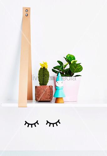 Hängendes Regal mit Häkelkaktus und Zimmerpflanze überm Wandtattoo