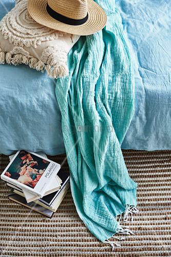 Sommerhut, Kissen und Schal auf dem Bett, daneben ein Bücherstapel