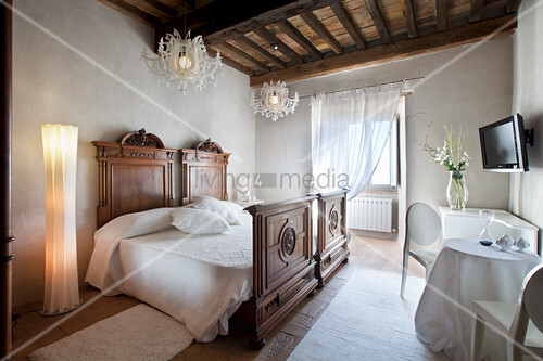 Antique wooden bed in simple bedroom in renovated château