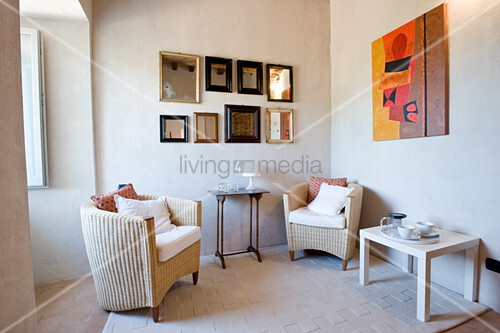 Rattan armchairs in seating area below collection of framed mirrors on wall