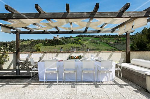 Terrassenplatz mit gedecktem Tisch unter Pergola