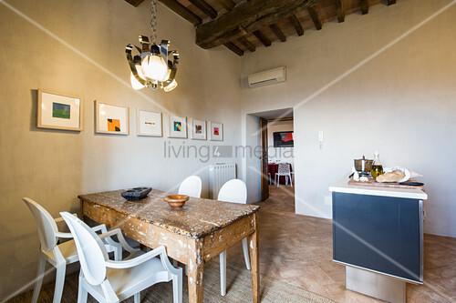 weiße Designerstühle am alten, fleckigen Holztisch in der Küche